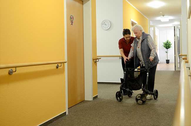 Seniorin unterstützt beim laufen mit Rollator - Altenheime Apel betreiben 5 Einrichtungen für Altenpflege & Seniorenbetreuung in Geesthacht, nähe Hamburg