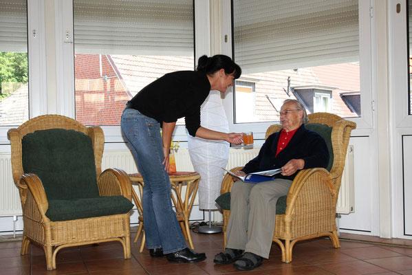 Senior bekommt Getränk von Pflegerin - Altenheime Apel betreiben 5 Einrichtungen für Altenpflege & Seniorenbetreuung in Geesthacht, nähe Hamburg